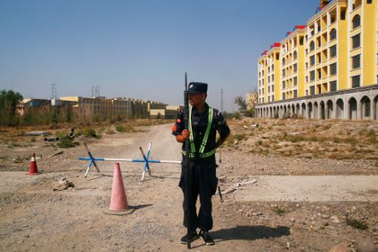 A Chinese police officer along the road near what is officially called the Professional Education Center in Xinjiang Uygur Autonomous Region, China, September 4, 2018. Photo taken September 4, 2018. REUTERS / Thomas Peter / File photo
