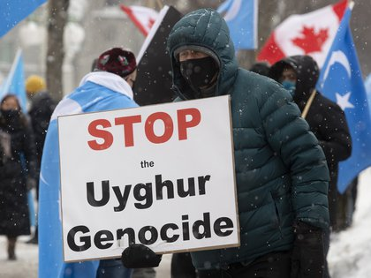 Protesters speak against China in front of parliament buildings in Ottawa, Ontario, for the genocide of the Muslim ethnic Uyghur community.  (Adrian Wilde / The Canadian Press via The Associated Press)