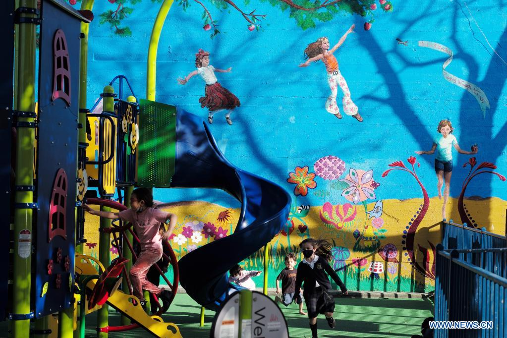 Children play in a reopened amusement park in California, United States