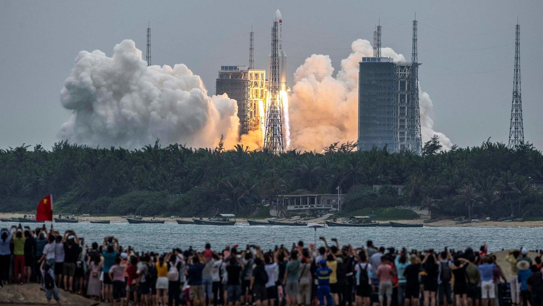 Dozens of people watch from the shore the launch of the Long March-5B Y2 rocket from the Wenchang Space Launch Center in Hainan, China.  April 29, 2021.