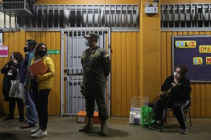 Election workers and the military wait while votes are stored at the end of the election day during elections for governors, mayors, councilors and members of the Constituent Assembly to draft a new constitution to replace Chile's constitution, in Santiago, Chile on May 15, 2021 Photo: Pablo Sanhoza - Reuters