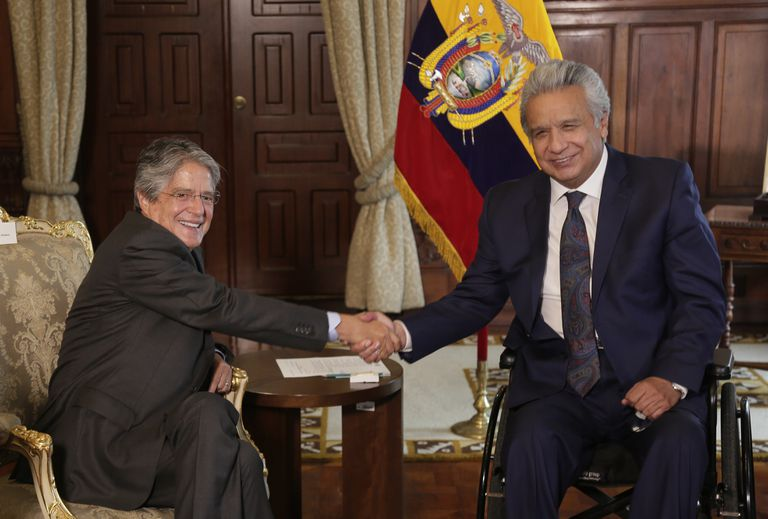 Ecuador's President Lenin Moreno, right, shakes hands with President-elect Guillermo Lasso during a meeting that is part of the presidential transition in Quito, Ecuador, on Monday, April 19, 2021