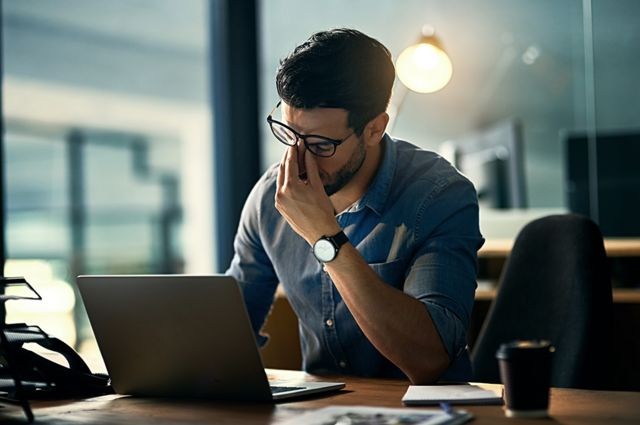 Exhausted man in front of a laptop