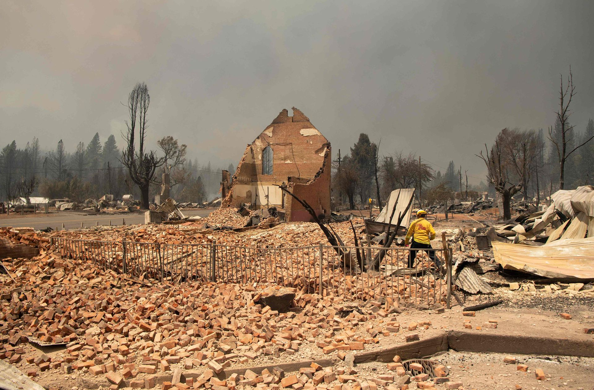 A firefighter inspects a historic building that burned during the Dixie Fire in downtown Greenville, California.  Greenville, is an Indian Valley settlement of a few hundred people dating back to the Gold Rush in the mid-19th century.  It was engulfed in flames as the wind directed hell towards the community, turning the sky orange