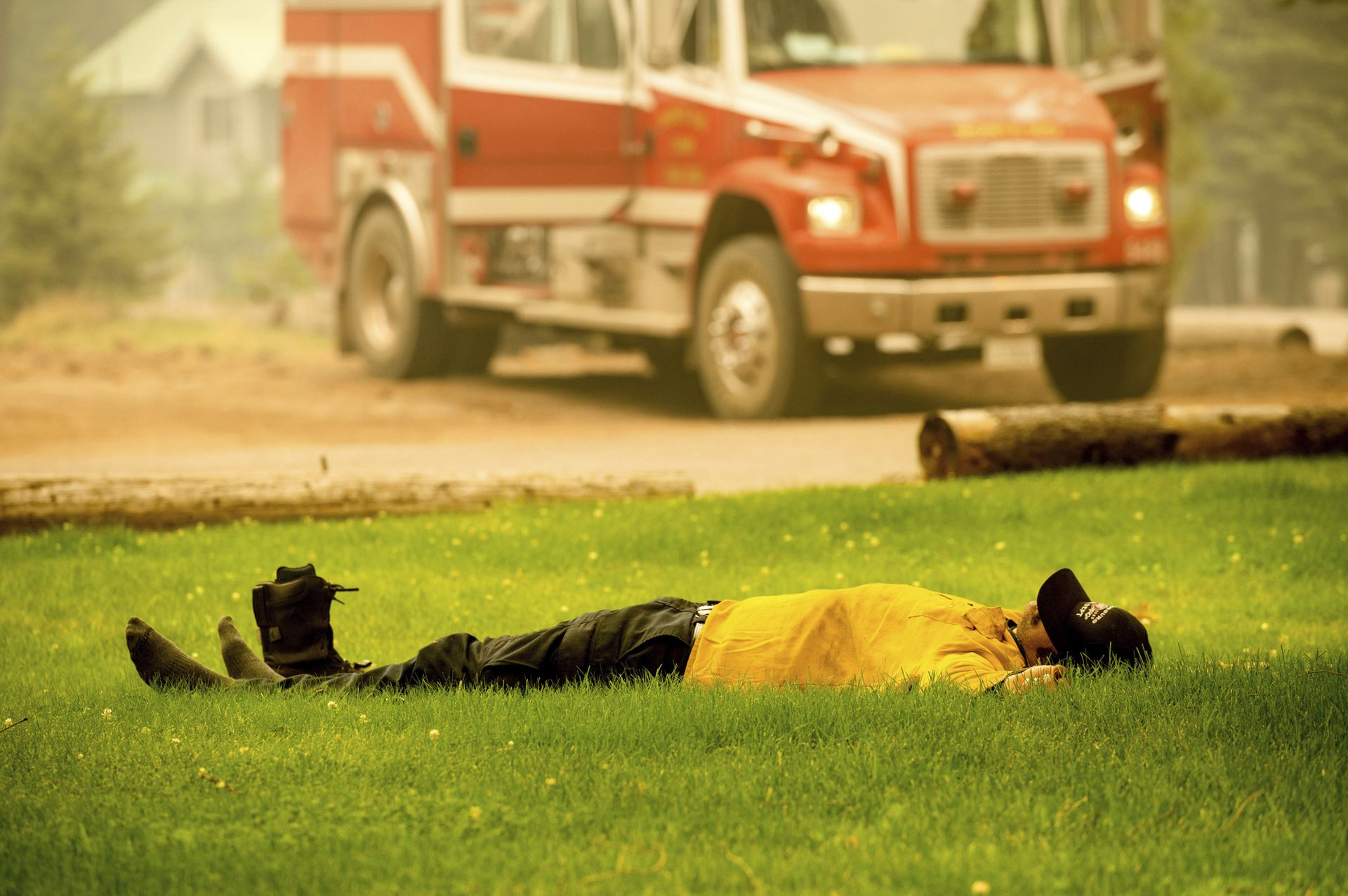 Healdsburg firefighter Justin Potter rests as his team prepares to fight the Dixie Fire in the Clear Creek community of Lassen County, California