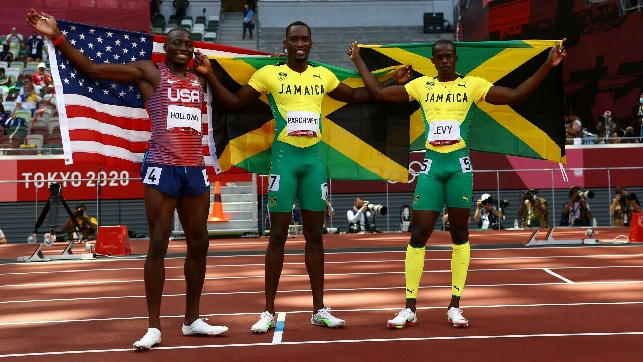 Hansley Parchman of Jamaica (centre) poses with his country's flag after winning the gold medal in the 110m hurdles.  Next to him is US silver medalist Grant Holloway and bronze medalist Ronald Levy.