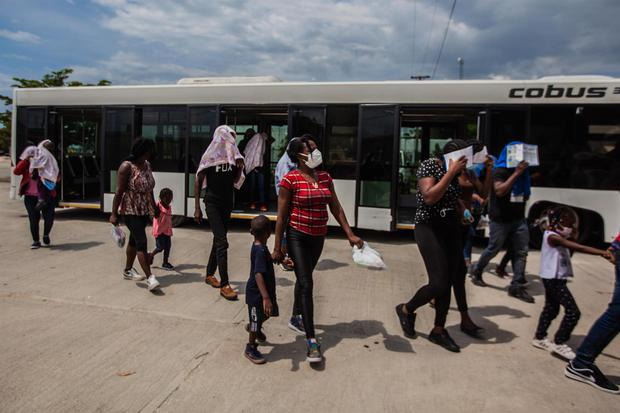 Haitian immigrants deported from the United States walk with their children after disembarking a plane at Toussaint Louverture Airport in Port-au-Prince.  (EFE/Richard Perrin).