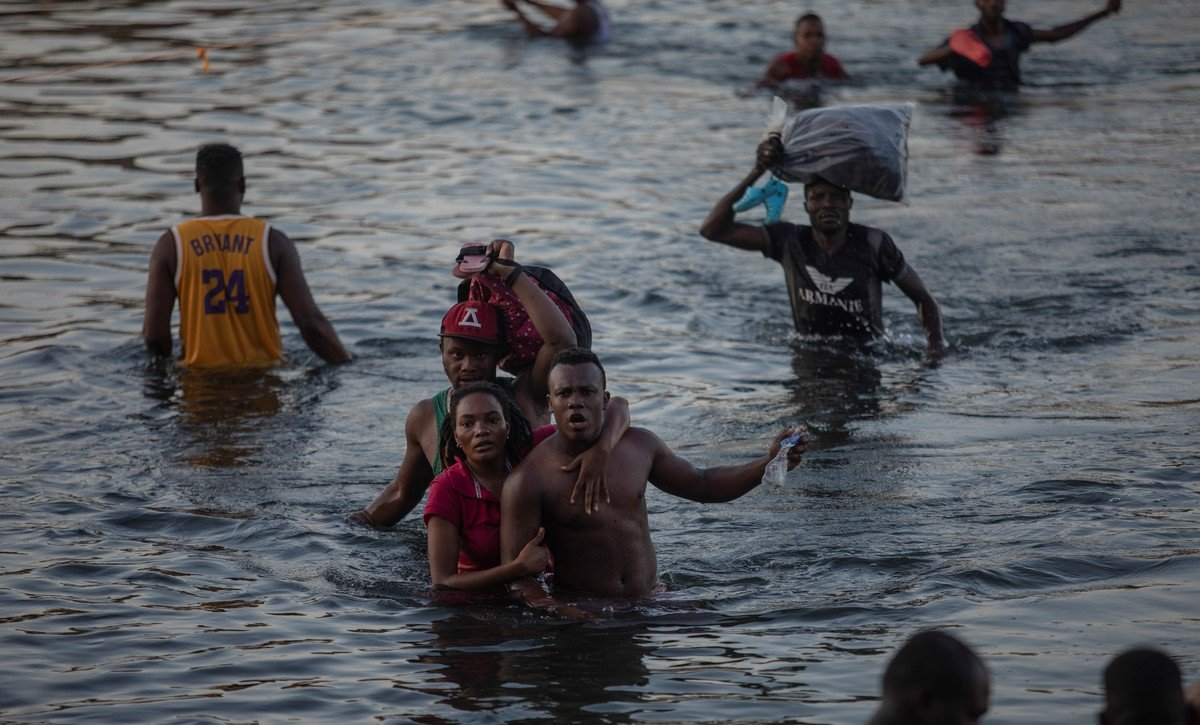 Some Haitians crossed the river with boxes full of food on their heads.  Photo: AP