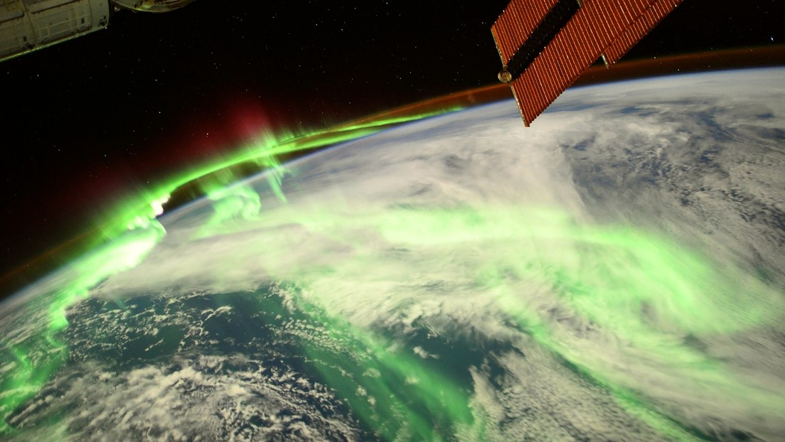 An astronaut shows a dazzling image taken from space of green and red aurora shining over Earth